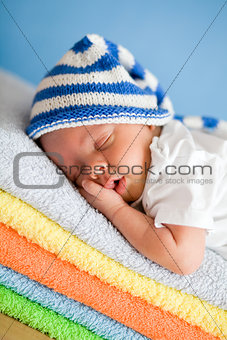 Sleeping newborn baby closeup portrait on colorful towels stack