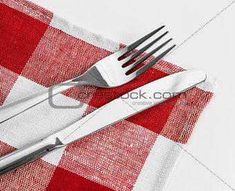 Knife and fork on red checked tablecloth