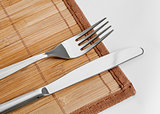 Knife and fork on bamboo tablecloth