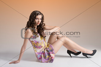 wavy brunette sitting on the floor touches her hair