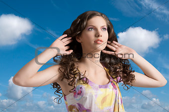 wavy brunette with colored dress with hands in the hair