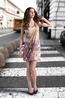 wavy brunette with colored dress looks at left