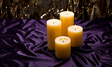 Four candles over purple velvet