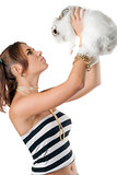 Pretty young woman playing with rabbit