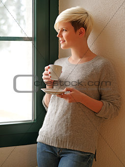 Looking out a window drinking coffee