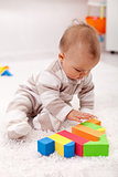 Baby girl playing eith wooden blocks