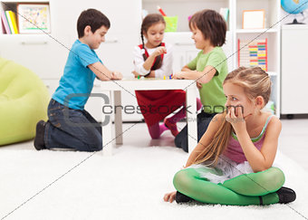 Little girl sitting apart - feeling excluded by the others