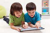 Boys playing labyrinth game on tablet computer