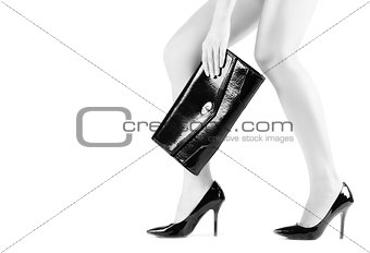 Beautiful slender womanish feet in black shoes and mini bag