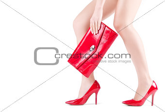 Beautiful slender womanish feet in red shoes and mini bag
