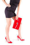 Slender beautiful womanish feet in red shoes and mini bag isolated