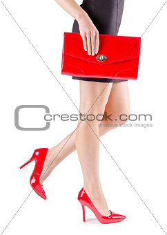 Slender beautiful womanish feet in red shoes and mini bag