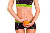 Slim figure of girl in a sportwear with orange in a hands