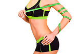 Slim figure of girl is in a sportwear with a centimetre ribbon on a hand