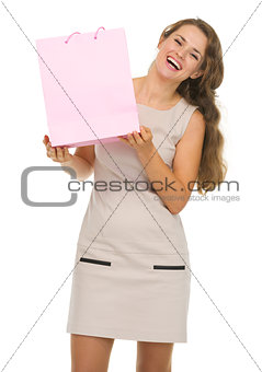Portrait of happy young woman showing pink shopping bag
