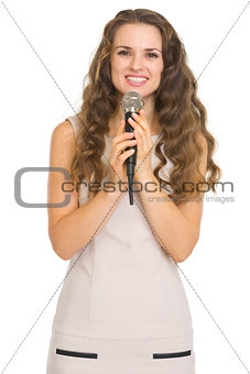 Portrait of smiling young woman with microphone