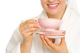 Closeup on smiling young woman in bathrobe with cup of tea