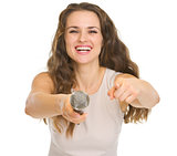 Happy young woman giving microphone and pointing in camera