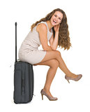 Smiling young woman sitting on wheels suitcase