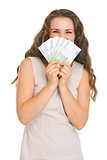 Happy young woman hiding behind fan of euros