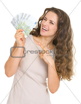 Smiling young woman pointing on euros