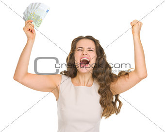 Happy young woman with euro banknotes rejoicing success