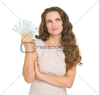 Thoughtful young woman holding fun of euro banknotes