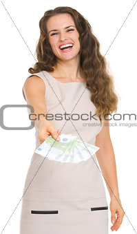 Smiling young woman giving fun of euro banknotes