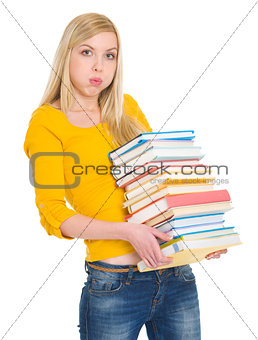 Tired student girl holding pile of books