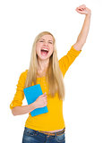 Happy student girl with book rejoicing success