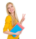 Happy student girl showing victory gesture