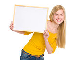 Happy student girl showing blank board