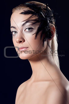 girl with feathered accessory and serious expression