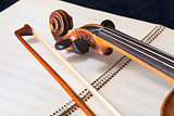 violin bow and scroll on music book