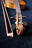 violin scroll and bow on black velvet