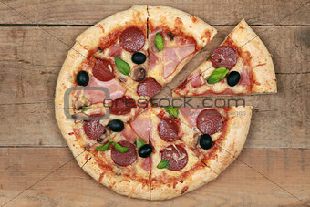 Sliced Deluxe Pizza on a wooden table