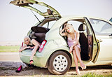 Two beautiful blonde girls sitting in broken car and waiting for help