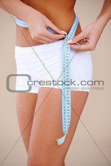 Close up of a woman measirung her waist