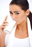 Woman is drinking milk from a glass