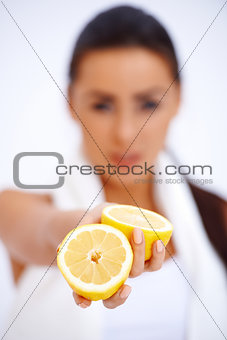 Close up of a woman showing fresh lemon