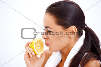 Woman holding lemon while making a face