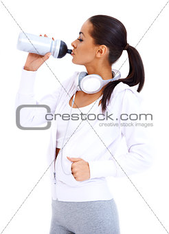 Sporty woman drinks from fitness bottle