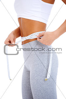 Close-up of slender woman measuring her waist