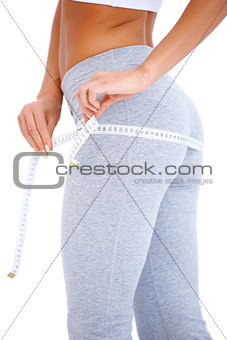 Close-up of slender woman measuring her body
