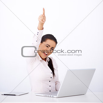 Happy woman sitting at her desk, with one arm rised