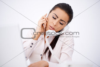 Woman talking by phones simultaneously