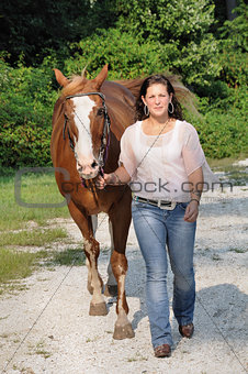 Young adult woman walking her horse