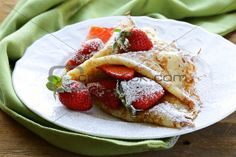 dessert crepes with strawberries and powdered sugar