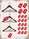 Set of hangers with tags and word sale on grunge background