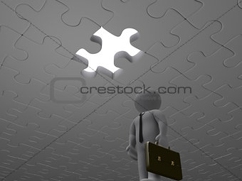 Businessman trapped under puzzle pieces